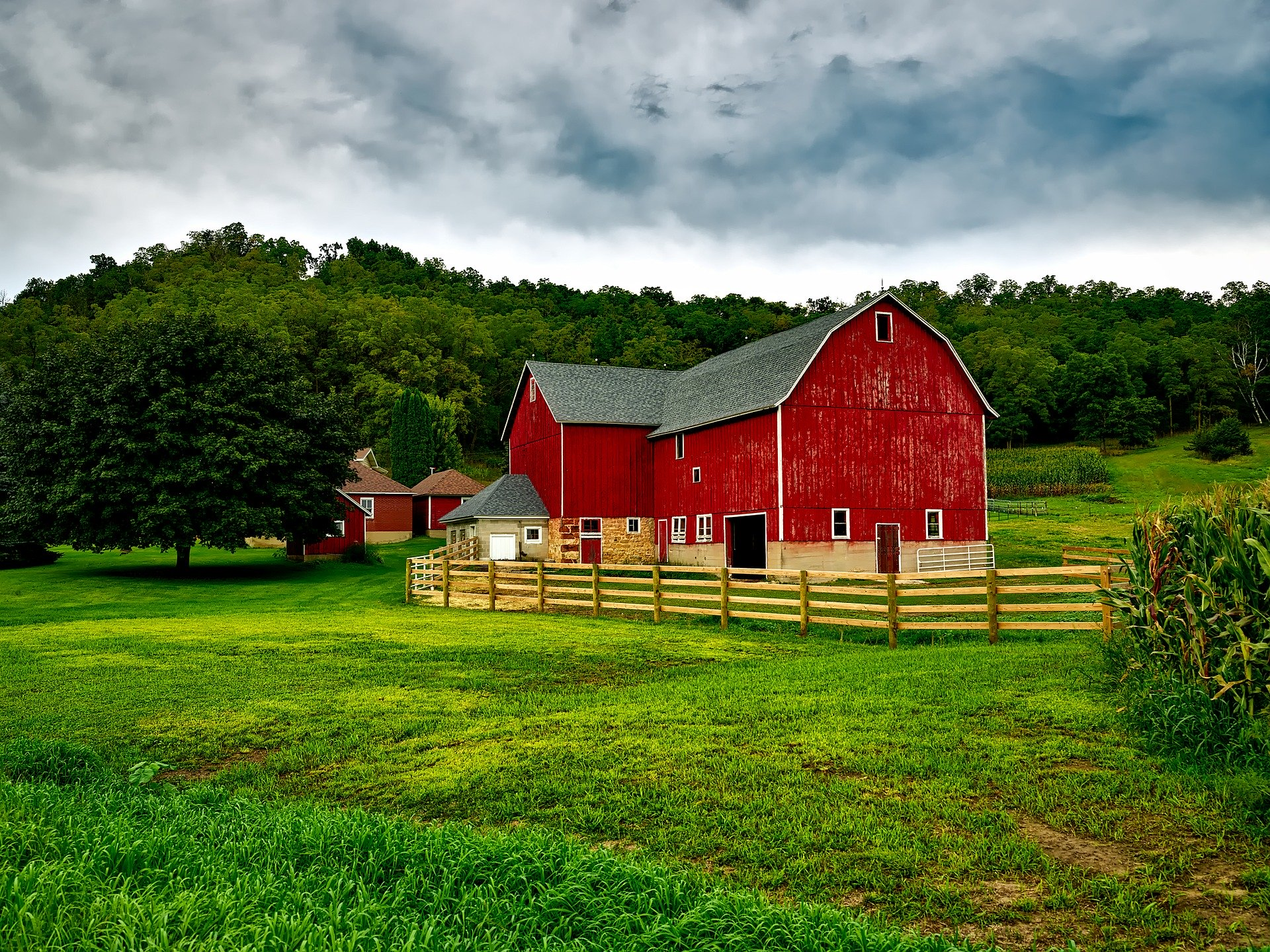 Beautiful Red Barn Next to a Brown Fence and Green Trees - Farm Background Wallpaper Pictures