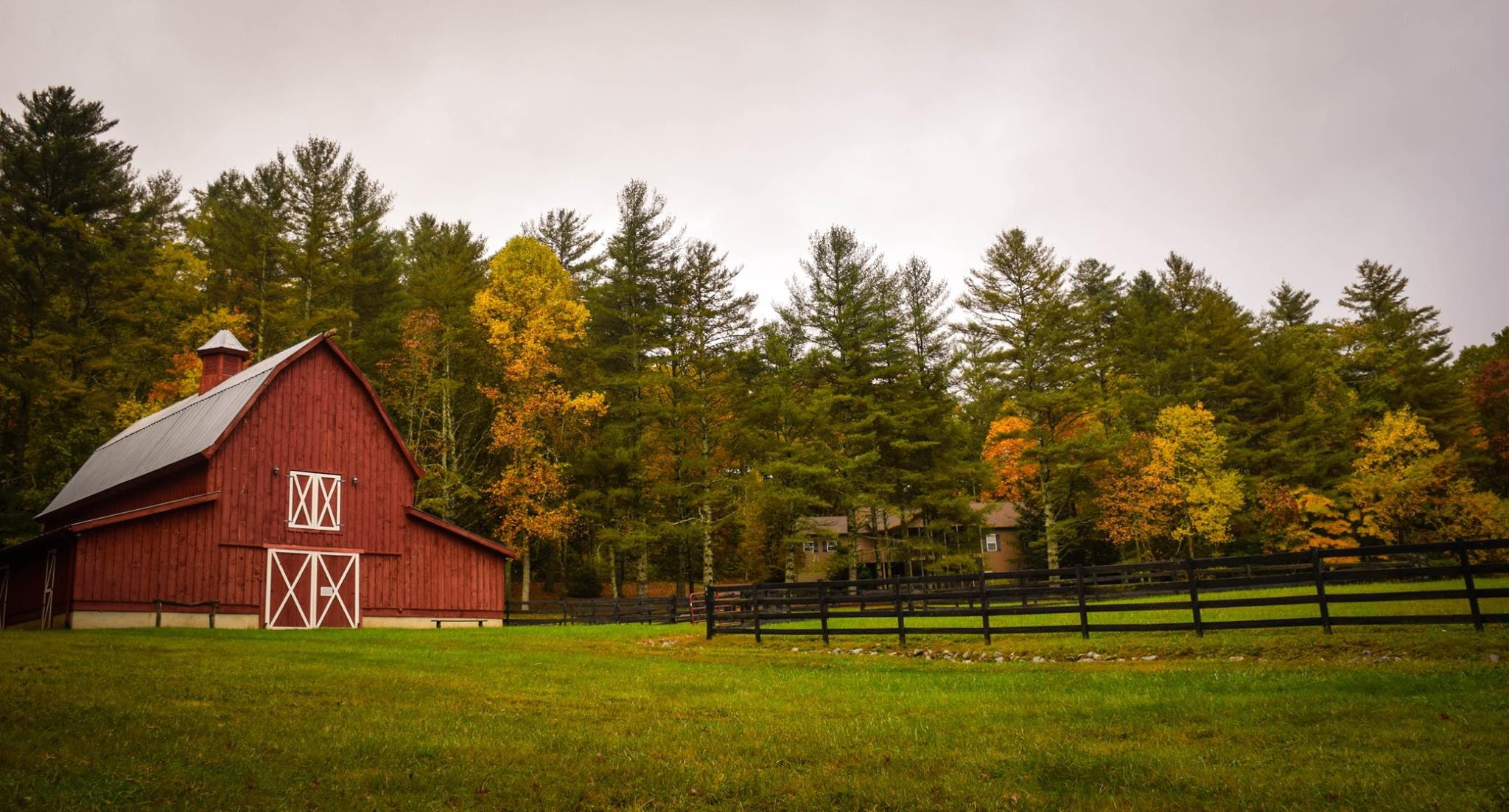 Beautiful Red Barn Next to Black Fence and Trees - Farm Background Wallpaper Pictures